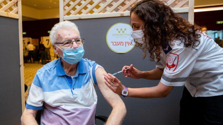 地中海タワーにある定年者コミュニティ居住者にCOVID-19ワクチンの初回投与を行うマーゲン・ダビド公社の職員