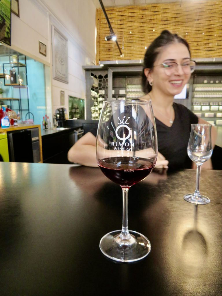 ビジターセンターマネージャーのLiron Ilus氏と、オリジナルのグラスに注がれたドライワイン。